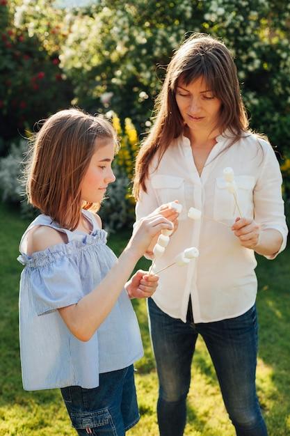 Moeder en dochter die heemstvleespen in tuin houden Gratis Foto