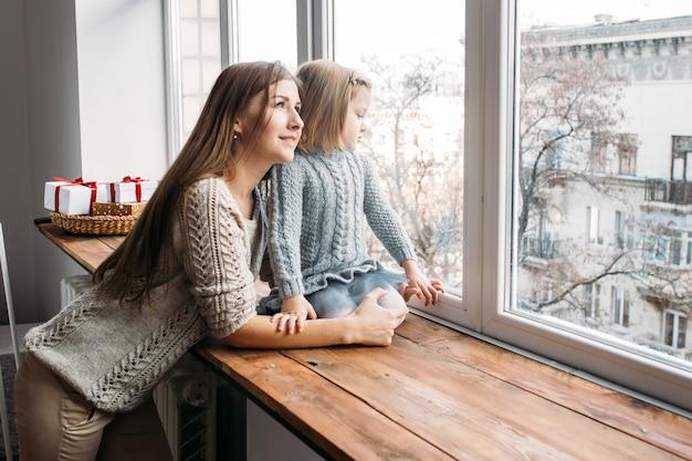 Moeder en dochter die in venster kijken. familie concept. Premium Foto