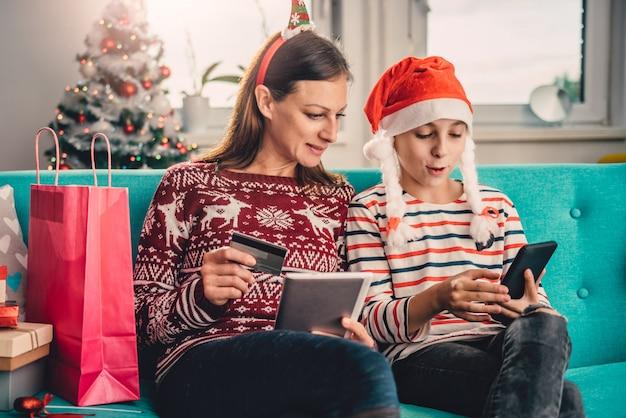 Moeder en dochter die online thuis tijdens kerstmis winkelen Premium Foto