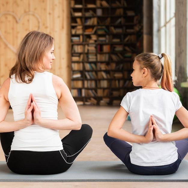 Moeder en dochter die op yogamatten mediteren die elkaar bekijken Gratis Foto