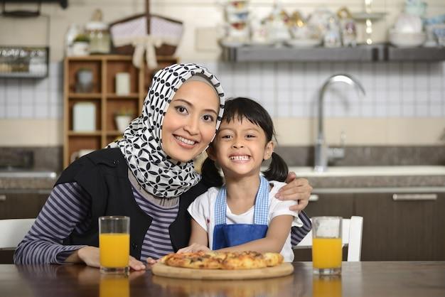Moeder en dochter die pizza eten Premium Foto
