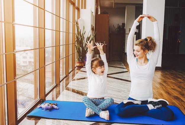 Moeder en dochter die yoga doen Gratis Foto
