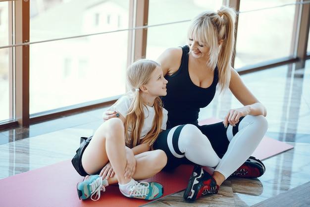 Moeder en dochter die yoga in een yogastudio doen Gratis Foto