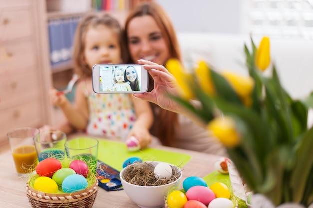 Moeder en dochter die zelfportret nemen terwijl pasen-tijd Gratis Foto