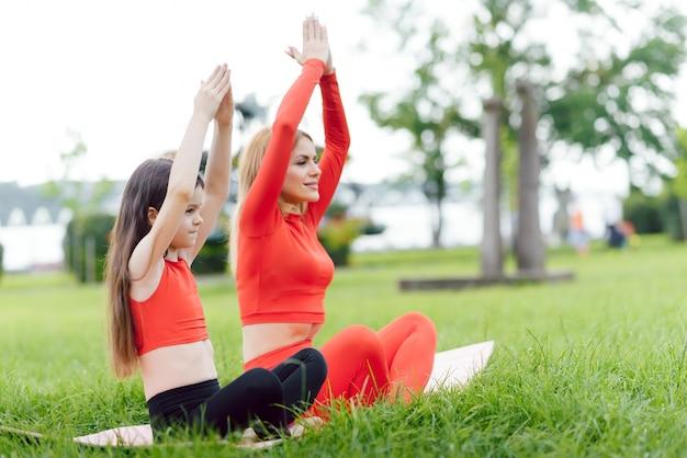 Moeder en dochter doen overdag yoga-oefeningen op gras in het park Premium Foto