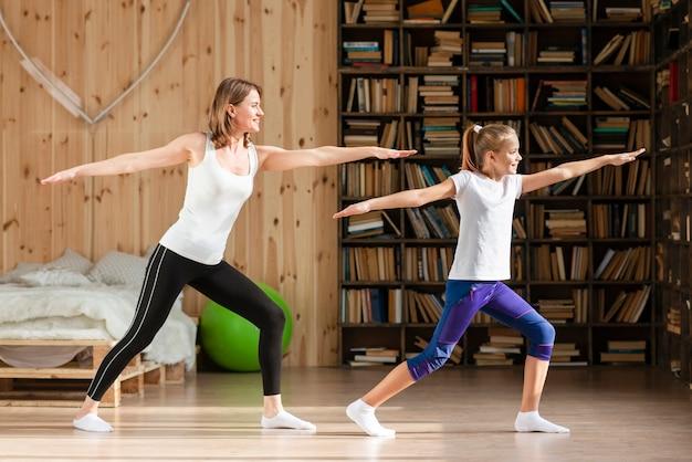 Moeder en dochter doen yoga pose Gratis Foto