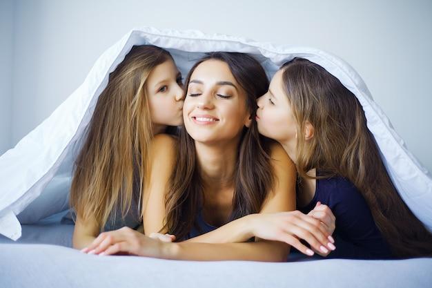 Moeder en dochter genieten thuis in bed Premium Foto