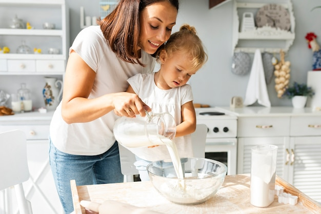Moeder en dochter gietende melk in een kom Gratis Foto