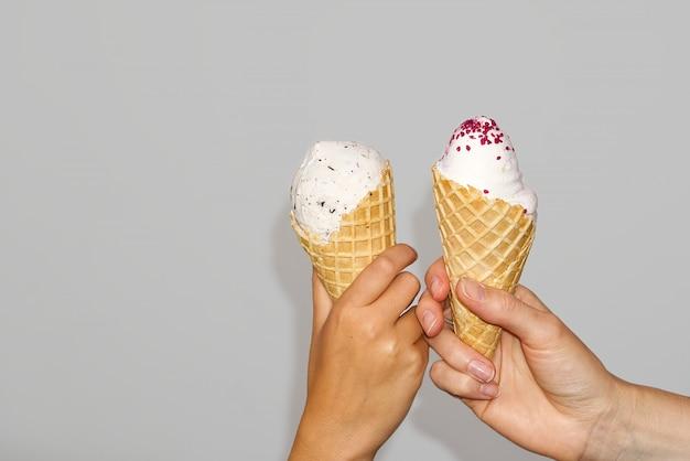 Moeder en dochter handen houdt ijs maïs met melkijs. geïsoleerd op een grijze muur Premium Foto
