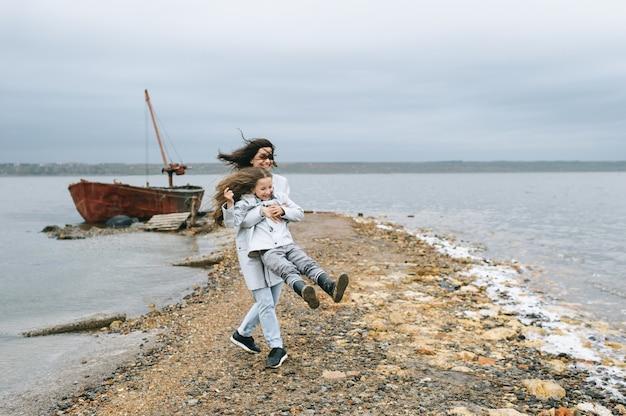 Moeder en dochter hebben plezier op de achtergrond van een boot in de buurt van het meer Premium Foto