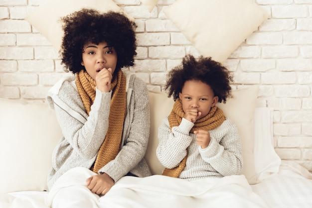 Moeder en dochter hoesten zittend op bed thuis. Premium Foto