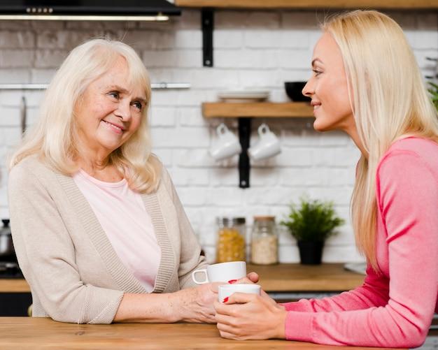 Moeder en dochter houden kopjes koffie en chatten Gratis Foto