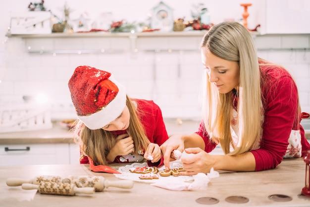Moeder en dochter in de keuken glazuur op peperkoekkoekjes in rode truien en kerstmutsen met verlichting Premium Foto