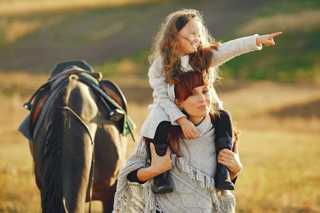 Moeder en dochter in een veld spelen met een paard Gratis Foto
