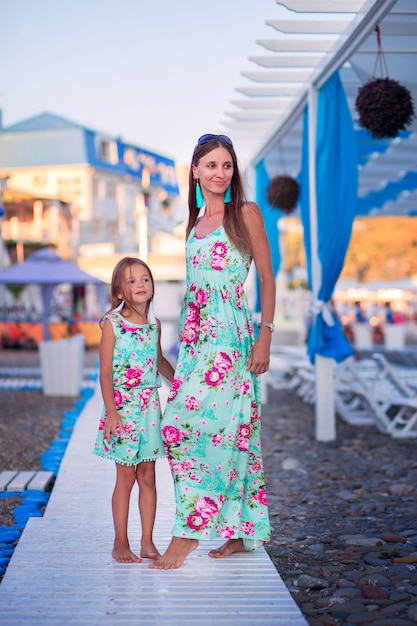 Moeder en dochter in identieke jurken lopen langs een houten pad op een kiezelstrand aan zee in het toeristische gebied Premium Foto