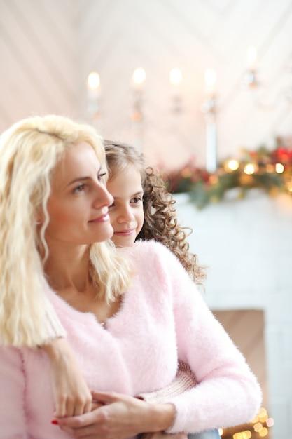 Moeder en dochter in kerst versierde woonkamer Gratis Foto