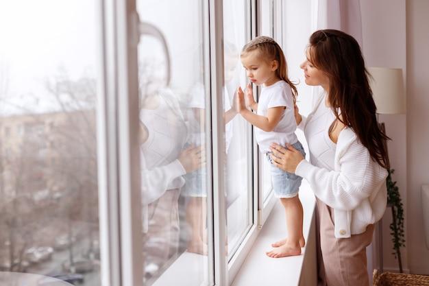 Moeder en dochter kijken naar buiten uit het raam Premium Foto