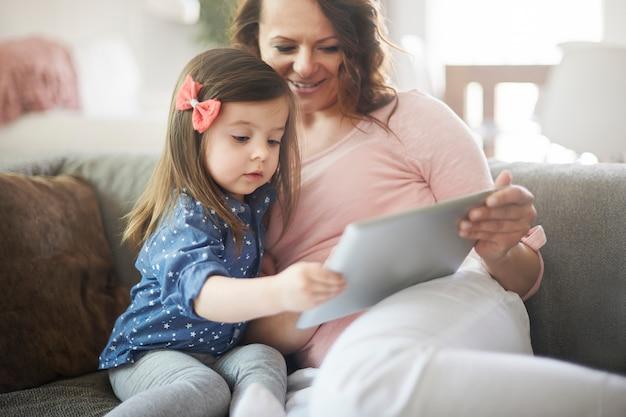 Moeder en dochter kijken naar video op een tablet Gratis Foto