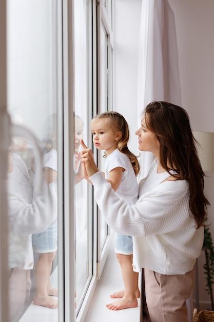 Moeder en dochter kijken uit het raam van het huis Premium Foto