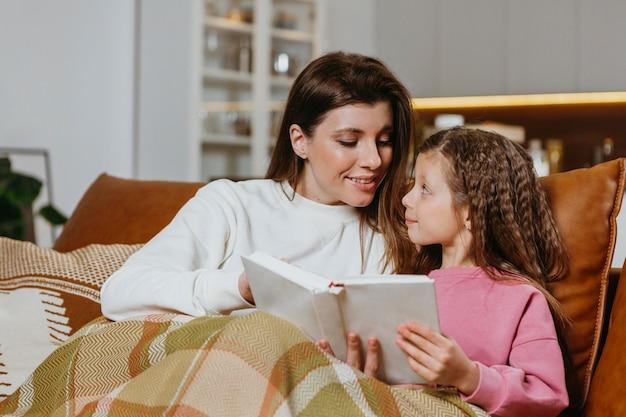 Moeder en dochter leesboek thuis Gratis Foto