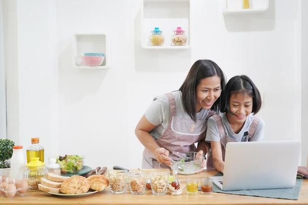 Moeder en dochter leren thuis koken met behulp van laptopcomputer in de keuken Premium Foto