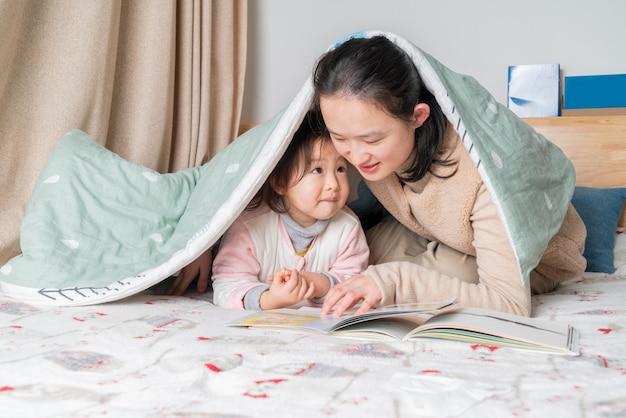 Moeder en dochter lezen in bed Premium Foto