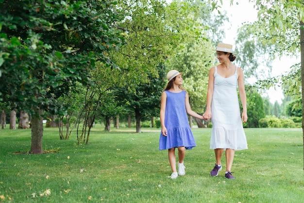 Moeder en dochter lopen samen buitenshuis Gratis Foto