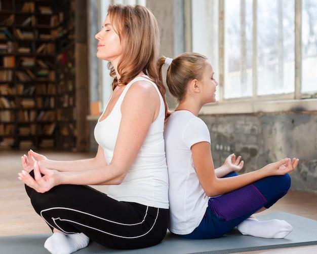 Moeder en dochter mediteren rug aan rug op yogamatten Gratis Foto