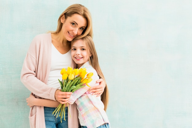 Moeder en dochter met en tulpen die koesteren glimlachen Gratis Foto