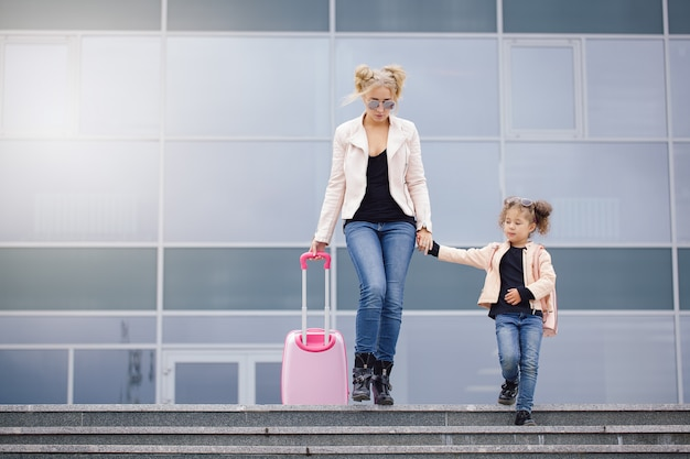 Moeder en dochter met roze bagage in roze jasje tegen de luchthaven. Premium Foto