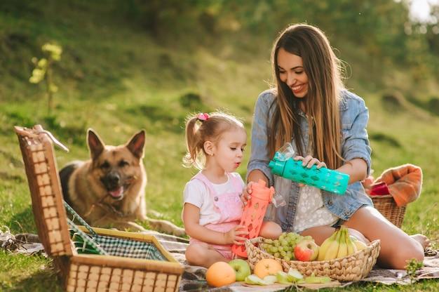 Moeder en dochter op een picknick met een hond Premium Foto