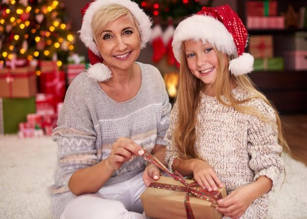 Moeder en dochter pakken wat kerstcadeaus uit Gratis Foto