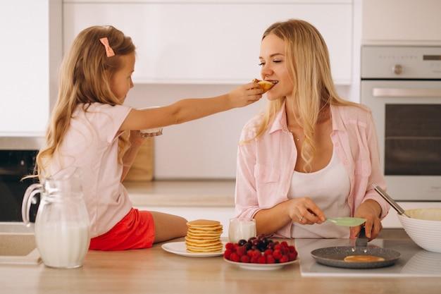 Moeder en dochter pannenkoeken bakken Gratis Foto