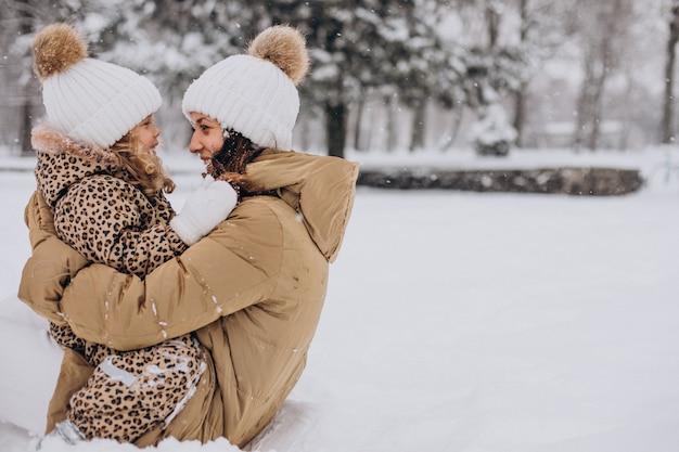 Moeder en dochter plezier in park vol sneeuw Gratis Foto
