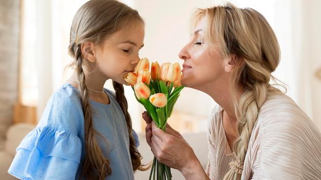 Moeder en dochter ruikend boeket tulpen Gratis Foto