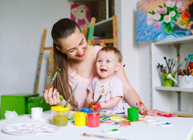 Moeder en dochter schilderen op canvas op de tekenschool. Premium Foto