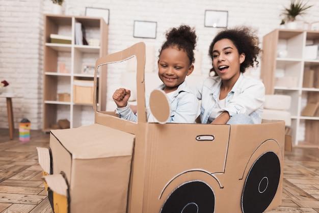 Moeder en dochter spelen met grote speelgoedauto's. Premium Foto