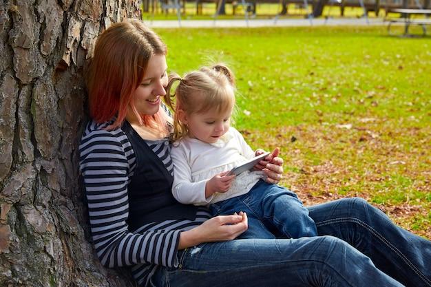 Moeder en dochter spelen met smartphone Premium Foto