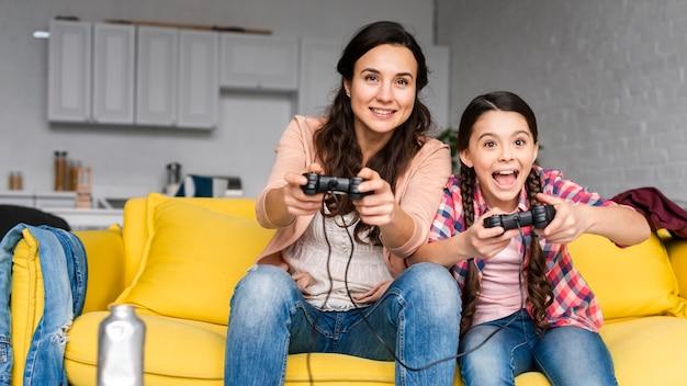 Moeder en dochter spelen samen videogames Gratis Foto