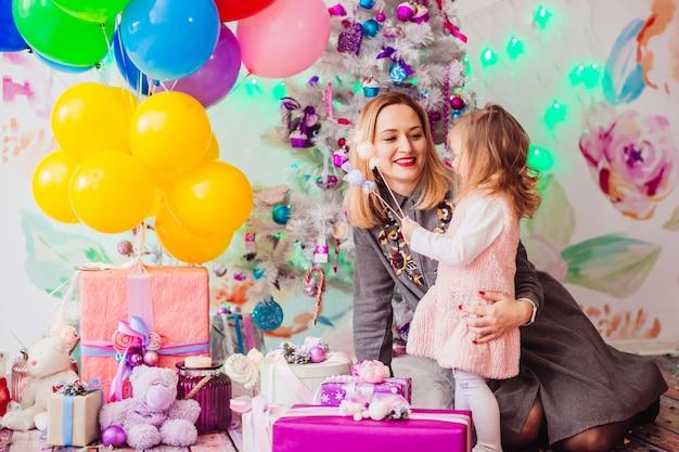 Moeder en dochter spelen voor een kerstboom in roze kamer Gratis Foto