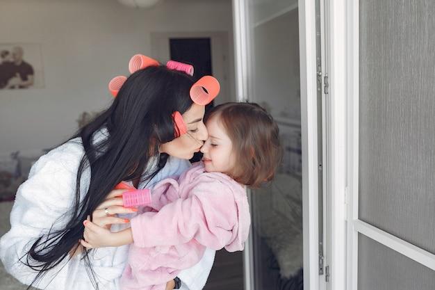 Moeder en dochter thuis met krulspelden op hun hoofd Gratis Foto