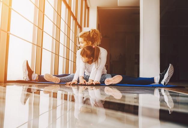 Moeder en dochter zitten op de vloer doen yoga Gratis Foto