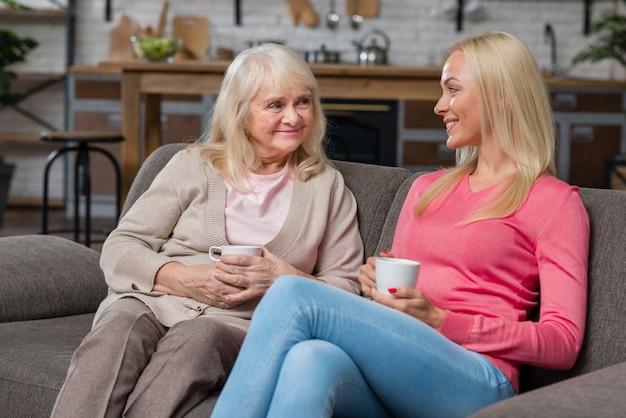 Moeder en dochter zittend op een bank en drink koffie Gratis Foto