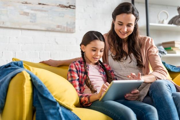 Moeder en dochter zittend op gele bank en lezen Gratis Foto