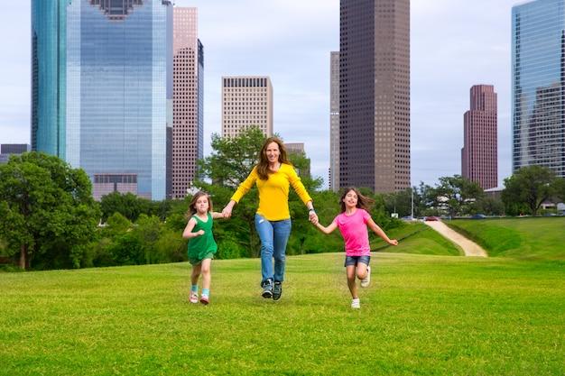 Moeder en dochters die holdingshanden op stadshorizon lopen Premium Foto