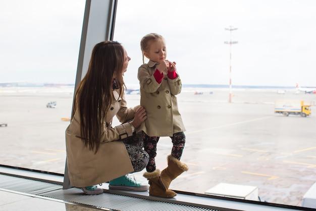 Moeder en dochtertje kijken uit het raam naar de luchthaventerminal Premium Foto