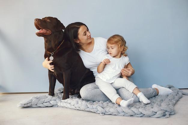 Moeder en dochtertje spelen met hond thuis Gratis Foto