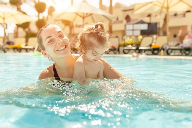 Moeder en dochtertje worden in het open zwembad gespeeld. Premium Foto