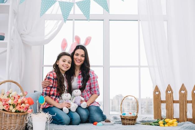 Moeder en dochterzitting die samen gevuld konijn houden op pasen-viering Gratis Foto