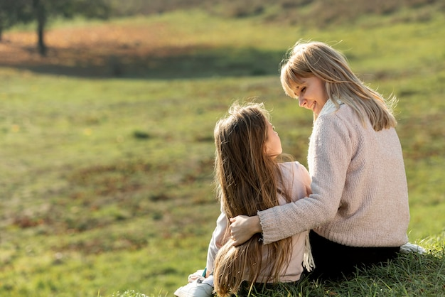 Moeder en dochterzitting in aard Gratis Foto
